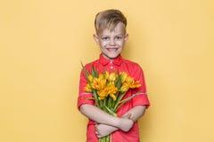Mały piękny dziecko z różową koszula daje bukietowi kwiaty na kobiety ` s dniu, Macierzysty ` s dzień Urodziny to walentynki dni  Obrazy Stock