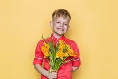 Mały piękny dziecko z różową koszula daje bukietowi kwiaty na kobiety ` s dniu, Macierzysty ` s dzień Urodziny to walentynki dni  Zdjęcia Royalty Free