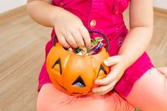 Mały piękny dziewczyny obsiadanie z banią z cukierkami w jej rękach na Halloween, zdjęcia royalty free