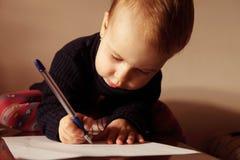 Mały piękny dziewczyny writing w jej książce Obraz Royalty Free