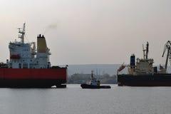 Mały pilotowy statek prowadzi wielkiego czerwonego ładunku statek przy portem morskim na bezwietrznym jesień dniu obrazy stock