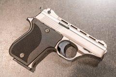 Mały pistolecik Odizolowywający na zmroku stole fotografia royalty free