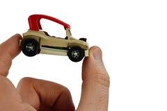 Mały plażowy zapluskwiony samochód zabawki model z czerwień dachem trzymającym między kciukiem i palcem wskazującym dorosła osoba Zdjęcia Stock