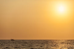 Mały połowu statek w niekończący się oceanie pod złocistym światłem słonecznym Fotografia Royalty Free