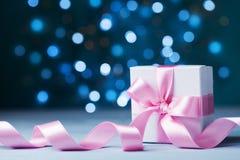 Mały prezenta pudełko, teraźniejszość z menchiami lub kłaniamy się faborek przeciw magicznemu bokeh tłu Kartka z pozdrowieniami d Zdjęcia Royalty Free