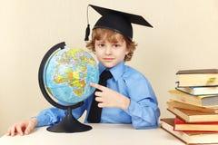 Mały profesor w akademickim kapeluszu pokazuje na kuli ziemskiej wśród starych książek Fotografia Royalty Free