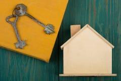mały puste miejsce dom, klucz na błękitnym drewnianym biurku i zdjęcia royalty free