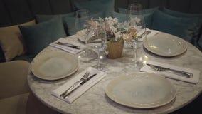 Mały round four-seater stół czekać na swój gości w nowożytnej wygodnej restauracji Wielka kanapa z wiele poduszkami wewnątrz zbiory wideo