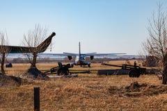 Mały samolot dla transportu pasażery i spadochroniarzi jest za ogrodzeniem wśród rarytasów artyleryjscy pistolety i zdjęcie stock