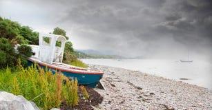 Mały shipwreck przy loch z kamień plażą Obrazy Stock