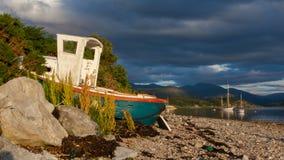 Mały shipwreck przy loch z kamień plażą Zdjęcia Stock