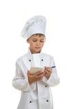 Mały skoncentrowany szef kuchni pisze puszkowi przepisie lub menu Biały tło obraz royalty free