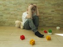 Mały smutny chłopiec obsiadanie na podłogowej wyrażeniowej czułości nieszczęśliwej blokowy depresji frustratedsadness Zdjęcia Stock
