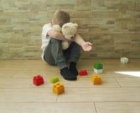 Mały smutny chłopiec obsiadanie na podłogowej wyrażeniowej czułości nieszczęśliwej blokowy depresji frustratedsadness Zdjęcie Royalty Free