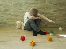 Mały smutny chłopiec obsiadanie na podłogowej wzburzonej czułości nieszczęśliwej blokowy depresji frustratedsadness Zdjęcie Royalty Free