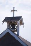 Mały stary dzwonkowy wierza z krzyżem na dachu małomiasteczkowy drewniany ch Obraz Stock