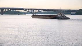 Mały statek holuje barki z ładunkiem na rzece w kierunku mostu zbiory