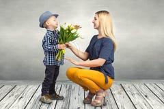 Mały syn daje jego ukochany matce bukietowi piękni tulipany Wiosna, pojęcie rodzinny wakacje dzień kobiety s zdjęcia royalty free