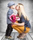 Mały syn daje jego ukochany matce pięknemu bukietowi różowe róże i całuje mum Wiosna, kobieta dzień, matka dzień fotografia stock