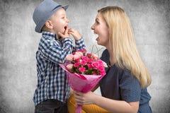 Mały syn daje jego ukochany matce pięknemu bukietowi różowe róże Wiosna, pojęcie rodzinny wakacje Kobiety ` s dzień, macierzysty  zdjęcie stock