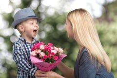 Mały syn daje jego ukochany matce pięknemu bukietowi różowe róże Wiosna, pojęcie rodzinny wakacje Kobiety ` s dzień, macierzysty  zdjęcia stock