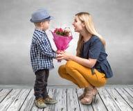 Mały syn daje jego ukochany matce pięknemu bukietowi różowe róże Wiosna, pojęcie rodzinny wakacje Kobiety ` s dzień, macierzysty  obraz stock
