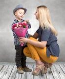 Mały syn daje jego ukochany matce pięknemu bukietowi różowe róże Wiosna, pojęcie rodzinny wakacje Kobiety ` s dzień, macierzysty  obrazy stock