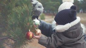 Mały syn i dekorujemy choinki outdoors Portret rodziny kochający zakończenie up Pojęcie Wesoło zbiory wideo