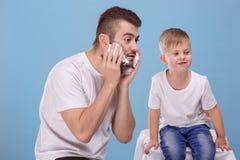 Mały syn i ojciec zabawę, tata rozmazy jego twarz z golenie pianą W łyżce suchy śniadanie fotografia royalty free