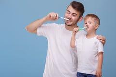 Mały syn i ojciec zabawę wpólnie, podczas gdy szczotkujący ich zęby z toothbrush niebieska tła obrazy stock