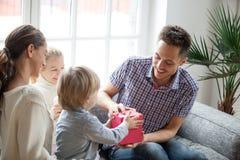 Mały syn przedstawia prezent dla tata, rodzinna odświętność ojcuje d Zdjęcie Stock
