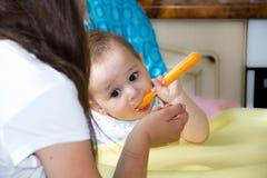 Mały szczęśliwy dziecka obsiadanie w krześle i je jogurt od czyj twarzy mąci w dziecka jedzeniu obrazy royalty free