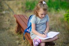 Mały szkolny chybienie siedzi krzyżujący nogi na parkowej ławce i coś należnie pisze w notatniku zdjęcie stock