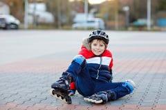 Mały szkolny dzieciak chłopiec łyżwiarstwo z rolownikami w mieście dziecko w ochrony bezpieczeństwie odziewa Aktywny ucznia robić zdjęcie stock