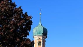 Mały Topiczny kościół Z purpura liśćmi Z niebieskiego nieba tłem fotografia stock