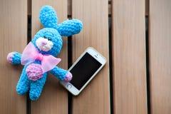 Mały trykotowy błękitny królik z smartphone na drewnianym tle trykotowa zabawka Amigurumi obrazy stock