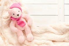 Mały trykotowy dziecko menchii zabawki niedźwiedź kłama na ciepłej koc zdjęcia stock