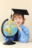 Mały uśmiechnięty profesor w akademickim kapeluszu z kulą ziemską Obraz Royalty Free
