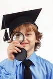 Mały uśmiechnięty profesor w akademickim kapeluszu z powiększać - szkło na białym tle Obrazy Royalty Free