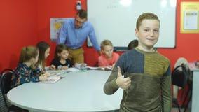 Mały uczeń gestykuluje aprobaty podczas gdy trzymający rezerwuje z kolega z klasy studiuje w tle zbiory