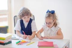 Mały uczeń i uczennica należnie robi ich pracie domowej fotografia royalty free