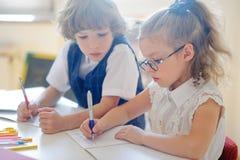 Mały uczeń i uczennica należnie robi ich pracie domowej zdjęcia stock