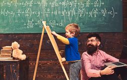 Mały uczeń z uśmiechniętym nauczycielem w sali lekcyjnej Bocznego widoku uroczy małe dziecko pisze na chalkboard uczenie się wcze obrazy stock