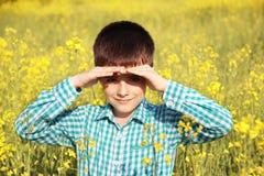 Mały uroczy chłopiec zez od słońca w żółtym polu Fotografia Stock