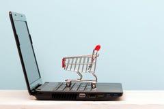 Mały wózek na zakupy na laptopie dla robić zakupy online Zdjęcie Royalty Free