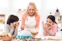 Mały wnuka i wnuczki spojrzenie jak babcia nalewa gotującego ciasto w pieczenie foremki Fotografia Royalty Free
