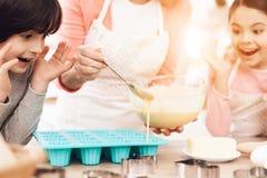 Mały wnuka i wnuczki spojrzenie jak babcia nalewa gotującego ciasto w pieczenie foremki Zdjęcia Stock