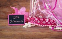 Małych dziewczyn partyjny strój obok małego chalkboard z zwrotem MAŁY BRIDESMADE: na drewnianym stole drużki lub czarodziejki kos Zdjęcie Royalty Free