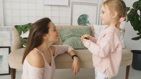 Małych dziewczynek kapiące medycyny w macierzystym ` s ostrożnie wprowadzać zbiory