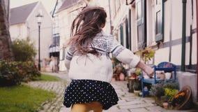 Małych dziewczynek spojrzenia przy kamerą, bieg na brukującej drodze widok z powrotem swobodny ruch Śliczny Europejski dziecko bi zdjęcie wideo